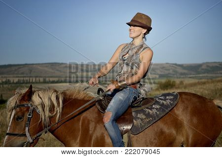Seductive stylish woman in brown hat on horse