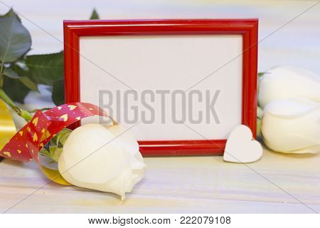 The concept of Love, Wedding, Proposal, Anniversary, St. Valentine's Day, Mother's Day with a red photo frame, whte roses and decorations on a light wooden table