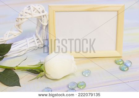 The concept of Love, Wedding, Proposal, Anniversary, St. Valentine's Day, Mother's Day with a wooden photo frame, whte roses and decorations on a light wooden table