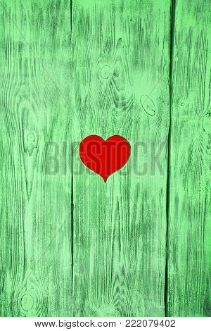 Red heart carved in a green wooden board. Background