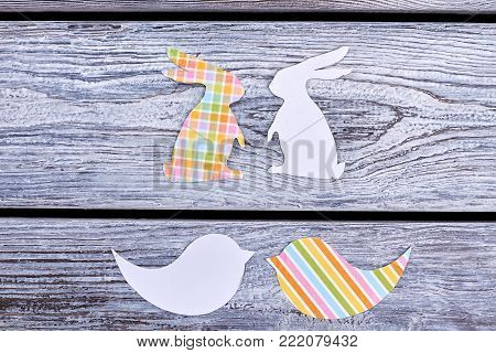 Cut out paper rabbits and birds. Papercut animalistic silhouettes. Color patterned paper figurines. Easter festive preparations.