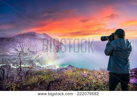 Photographer or Traveller using a professional DSLR camera take photo beautiful landscape of Kawah Ijen at Sunrise. The most famous tourist attraction in Indonesia - Recreation and outdoor travel concept.