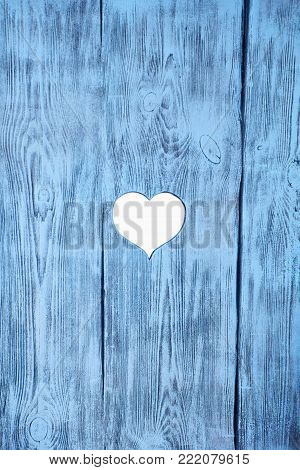 White heart carved in a blue wooden board. Background. Postcard, valentine