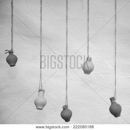 On an old clay wall hang vases on ropes, like decor.