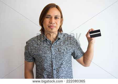 Closeup portrait of content young Asian man looking at camera and showing business card. Introduction concept. Isolated front view on grey background.
