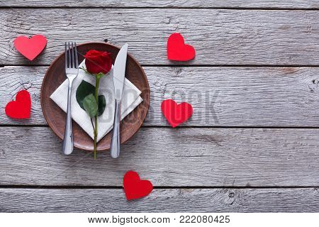 Valentine day background. Top view of restaurant wooden table with cutlery and rose on plate and paper hearts. Copy space on rustic wood. Valentine's Day, love, romantic concept