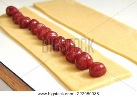 Preparation of cookies in the form of sticks with cherry filling for the cake Monastic cottage. The cookies are lying on a white kitchen table.