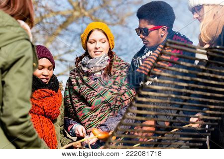 Multi-ethnic group of five young people having fun at barbecue in winter