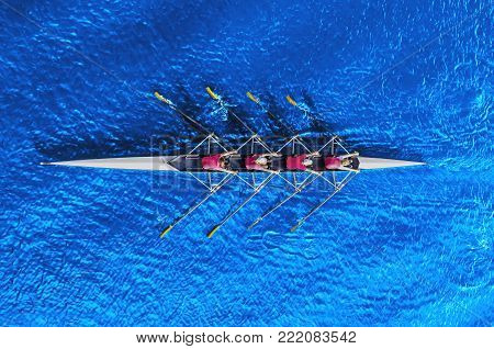 Women's rowing team clopse up on blue water, top view