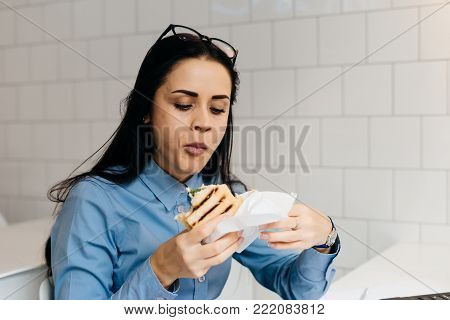 young black-haired girl in a blue shirt eagerly eats a sandwich in a cafe