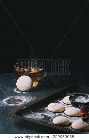 Homemade almond cookies with sugar powder, with vintage sieve, on old oven tray and cup of hot tea over dark blue wooden table. Dark rustic style. Top view, space