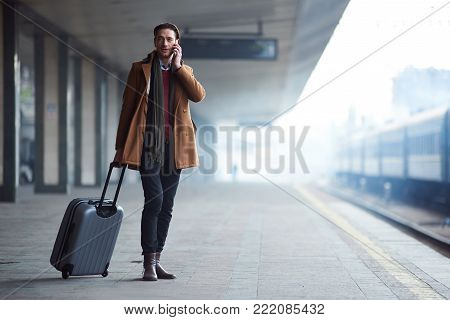 Full length portrait of serene man telling by mobile while walking with baggage along railway station. Communication concept. Copy space