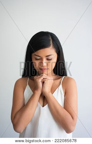 Closeup portrait of serious young pretty Asian woman clasping hands and praying. Prayer concept. Isolated front view on grey background.