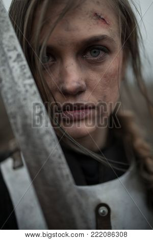 Portrait of girl in image of Jeanne d'Arc with wounds on her face in armor and with sword in her hands.