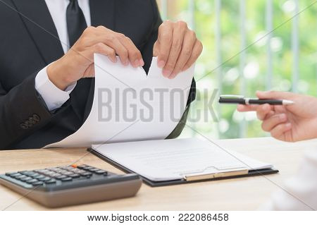 Hands of businessman ripping agreement paper when woman giving a pen for signing, break the rules - failure business concept.