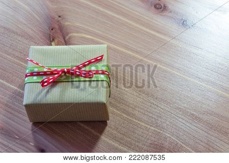 Tiny gift box wrapped in rustic brown kraft paper with red and green ribbons, simple bow, copy space, wood table, horizontal aspect