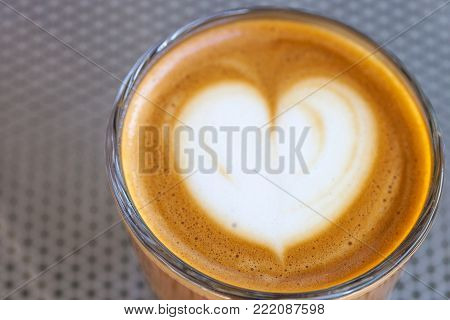 Top view of cortado coffee in a glass with the foam in shape of heart