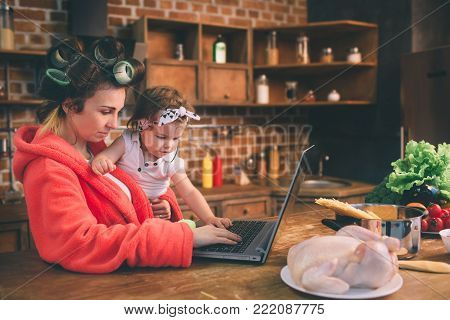 Mum at home. Young mother with little child in the home kitchen. Woman doing many tasks while looks after her baby. She is Using a laptop PC Technology and Maternity.