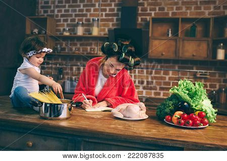 Mum at home. Young mother with little child in the home kitchen. Woman doing many tasks while looks after her baby. She talking on a cell phone or smartphone, writing a pen to do list in a notebook