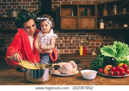Stressed mum at home. Young mother with little child in the home kitchen. Woman doing many tasks while looks after her baby.