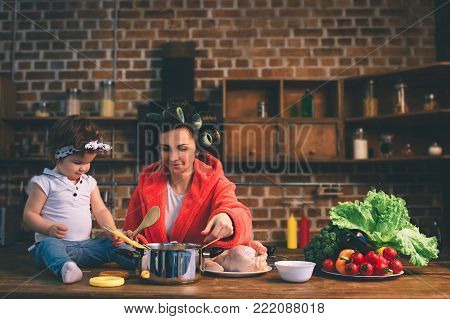 Mum at home. Young mother with little child in the home kitchen. Woman doing many tasks while looks after her baby. They are cooking tasty food together