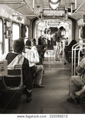 Turin, Italy - March 21, 2011: People travelling inside a tram in Turin, Italy. Commuters traveling in an old vintage tram.