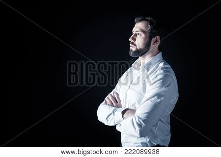 Handsome look. Serious nice bearded man standing cross handed and looking in front of him while being thoughtful