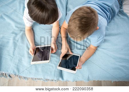 Top view of youngsters lying on blanket and holding devices in their hands