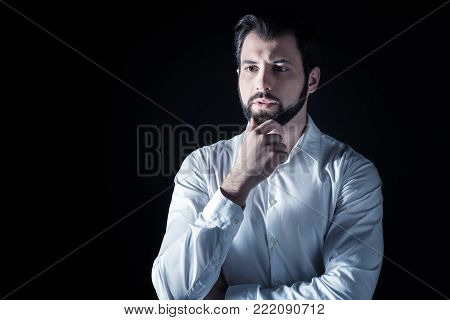 Pensive look. Smart nice handsome man standing against black background and thinking while looking for a solution