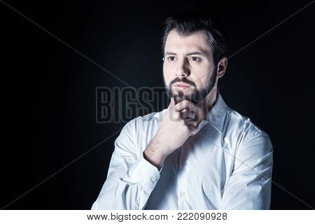 Time to think. Serious handsome smart man holding his chin and focusing on his thoughts while having a lot to think about