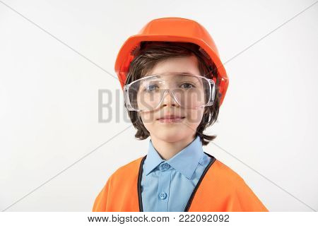 Portrait of dreamy kid preparing to become an architect. He is wearing orange helmet and safety glasses. Isolated on background