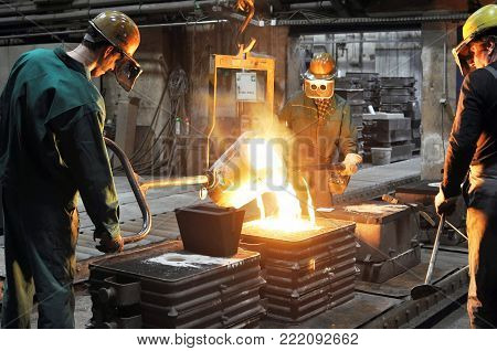 Workers in a foundry - production of steel castings in an industrial company