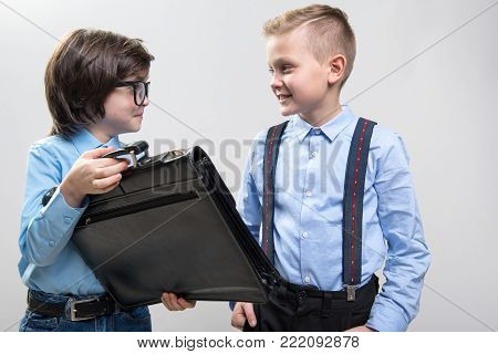Waist up of two smart children in formal clothing playing in business. Isolated on background