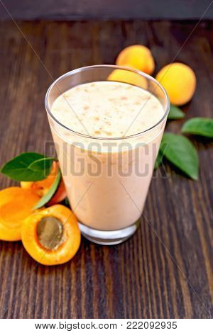 One tall glass of milkshake with apricots, mint on the background of a wooden board