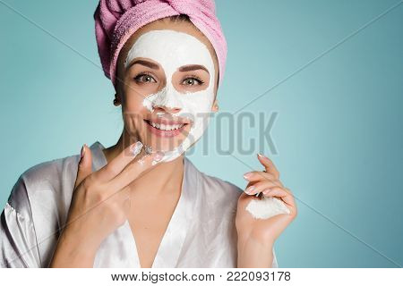 a smiling happy girl with a pink towel on her head puts on her face a white moisturizing mask