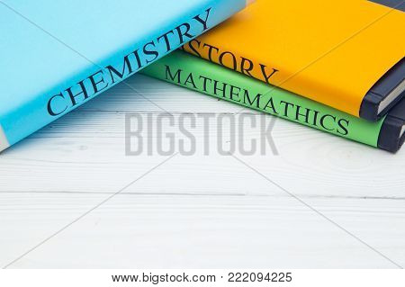 Education concept: school books on different subjects in bright covers on a white wooden table, space for a text or product display