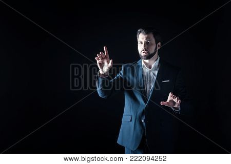 Sensory screen. Serious nice bearded businessman standing in front of the sensory screen and pointing with his finger while using it