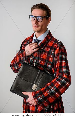 Waist up portrait of successful guy holding briefcase and adjusting tie. He is looking at camera. Isolated on grey background
