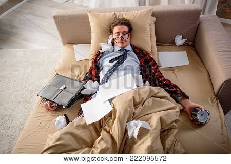 Serene man lying on the sofa, his eyes are closed with calm smile. He is having alarm clock and briefcase in his hand. Overwork concept