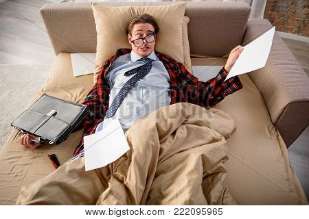 Unhappy guy is in bed and shocked by the amount of work. He is holding piece of paper and briefcase