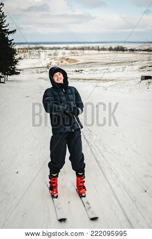 Men rides, rises on a ski lift, on skiing a on snow in Carpathian mountains. On background forest and ski slopes. Close up. Winter nature. The man rides at speed on snow.