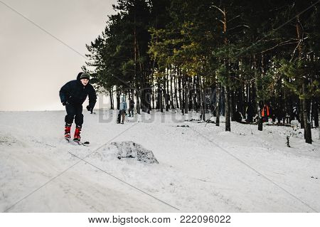 Men rides on skiing jumps from a hill from a springboard ski-jump on snow in Carpathian mountains. On background forest and ski slopes. Close up. Winter nature. The man rides at speed on snow.