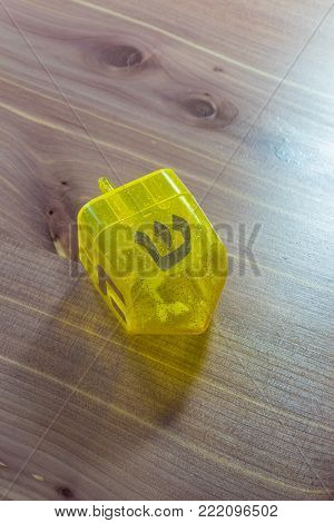 Yellow translucent plastic Hanukkah dreidel on a wood table, Hebrew letter Shin facing up, copy space, vertical aspect