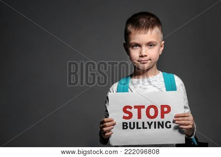 Little boy holding paper with text STOP BULLYING on dark background