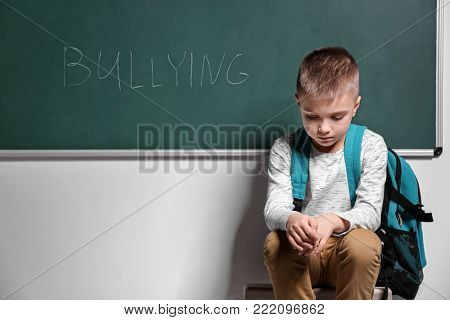 Little boy near chalkboard with word BULLYING indoors