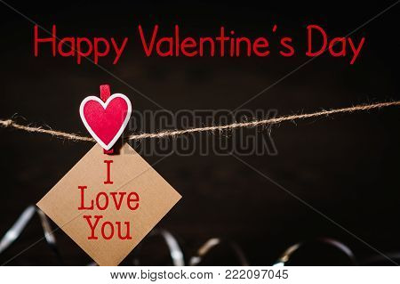 Text happy Valentine's Day. Craft paper, one blank, with red heart hanging on lacing or rope with space. Place for text. concept of St. Valentine's Day. International Women's Day, eighth of March.