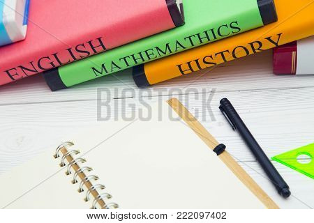 Education concept. Studying for exams English, Mathematics, History, student books and stationary on a white wooden table, space for a text or product display