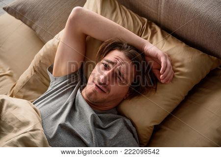 Exhausted adult male looking at camera with weary look while lying in bed at home. Top view