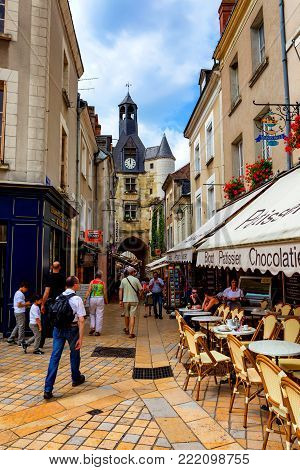 AMBOISE, FRANCE - CIRCA JUNE 2014: Narrow street of Amboise with tourists and cafes on sunny day. Amboise is a popular site in France with ancient castles