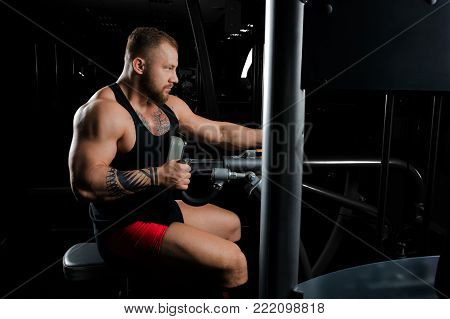 The Athlete Performs An Exercise On The Latissimus Muscles Of The Back On A Special Device.